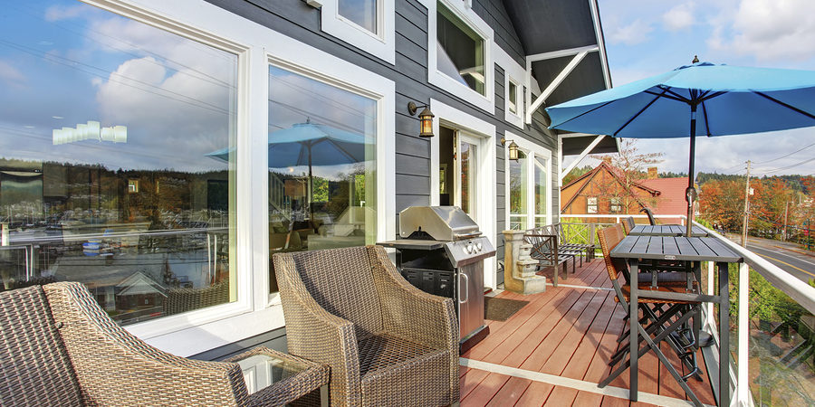 Northwest traditinal wooden deck with large windows chairs and tables.